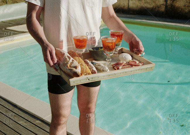 Person standing next to a swimming pool holding a tray with bread, cured meats, and iced tea