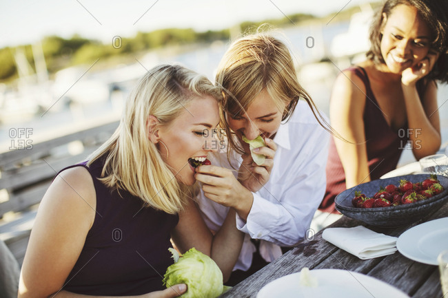 Young woman looking at cheerful blond friends sharing cabbage at picnic table
