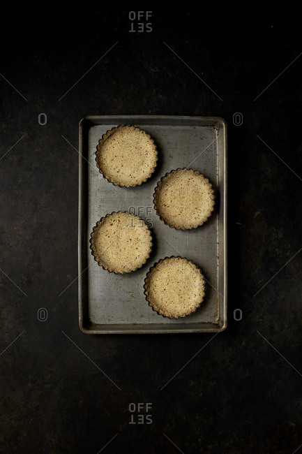 An empty pastry tart base on a cooking tray