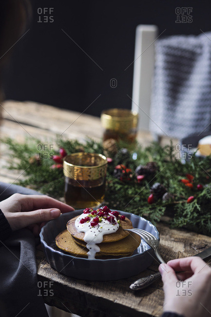 Christmas breakfast table: Woman eating pumpkin pancakes with yogurt cream and currant