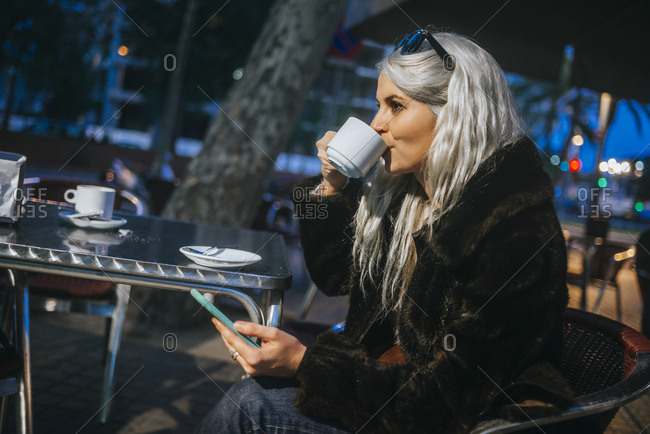 Woman with white hair drinking coffee with mobile phone in hand