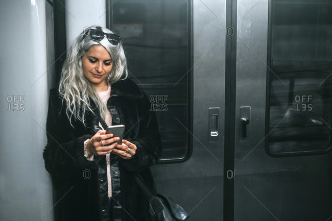 Woman with white hair texting on mobile phone while traveling by subway