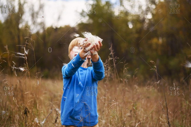 Young boy playing with weeds in tall grass