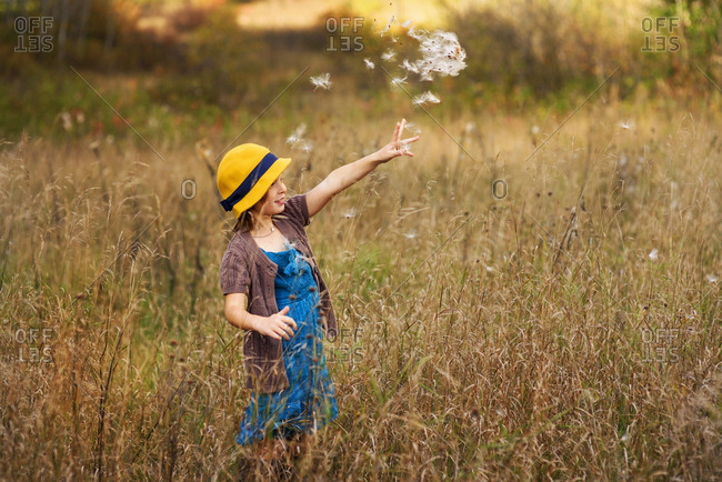 Young girl playing with weeds in a field