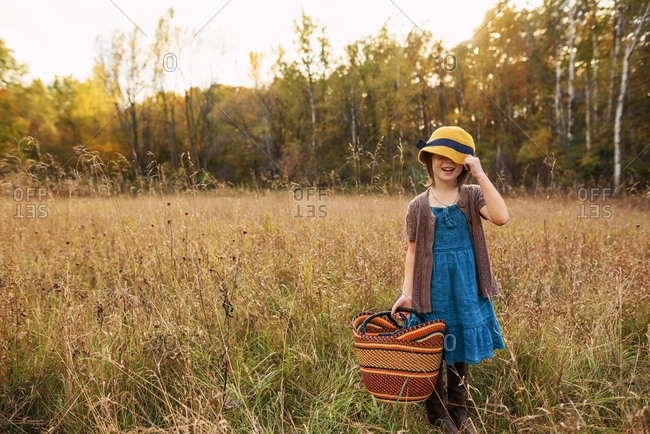 Young girl in a field with a woven basket