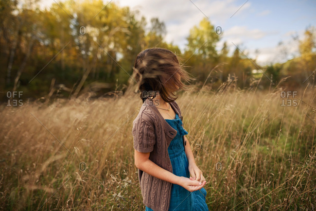 Young girl in a windy field