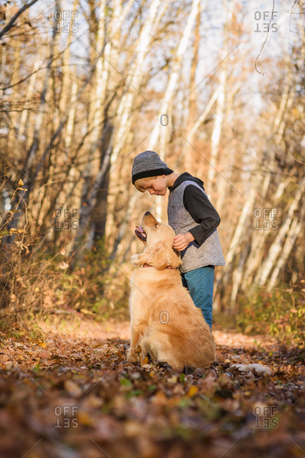 Young boy pets his golden retriever