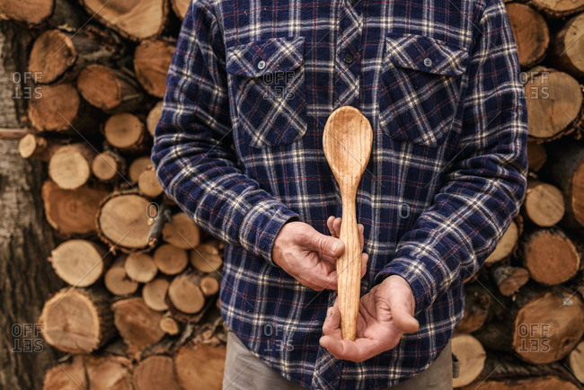 Man holding a hand carved wooden spoon