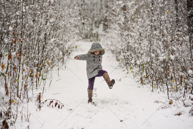 Young girl stomps on a snowy winter trail