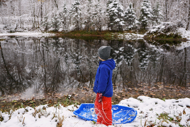 Young boy takes his sled to the water edge