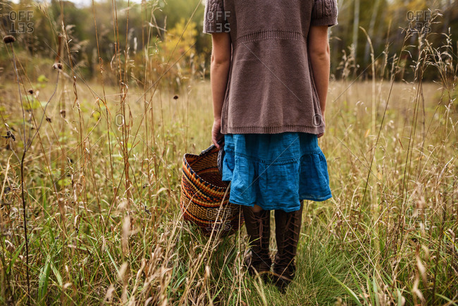 Young girl stands in a fall field