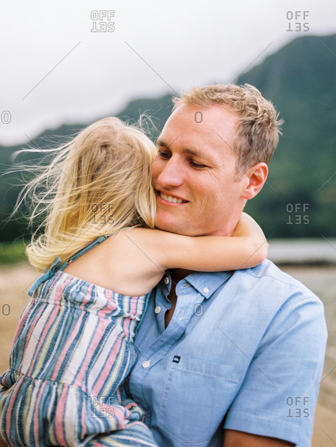 Little girl with her arms around father's neck