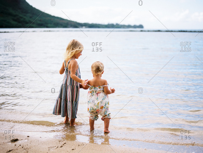 Sisters wading in the water together at beach