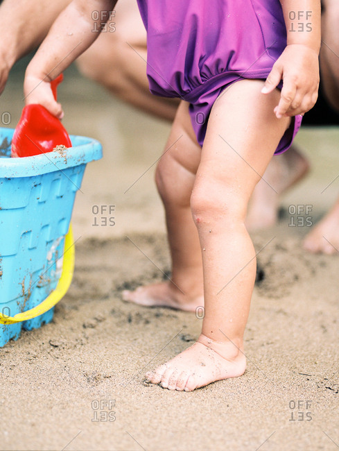 Barefoot toddler girl scooping sand into bucket on beach