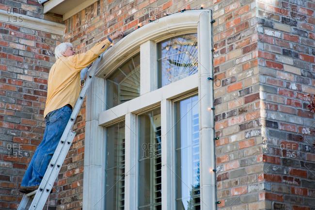Senior Man On A Ladder Hanging Christmas Lights Over A