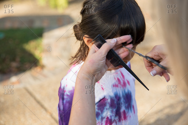 Woman trimming a little girl's bangs