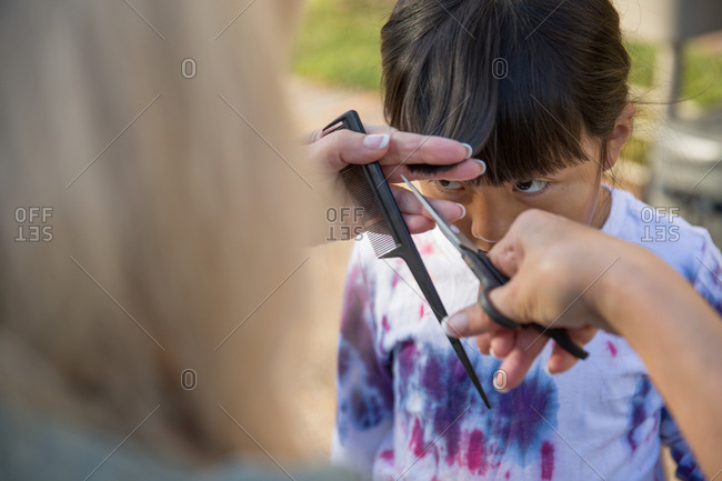 Woman trimming girl's bangs
