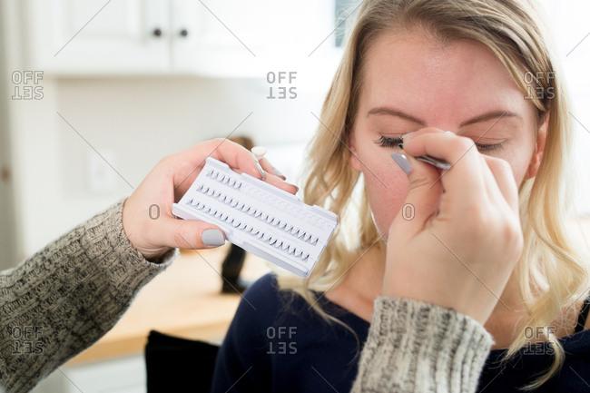 Makeup artist applying eyelashes to woman