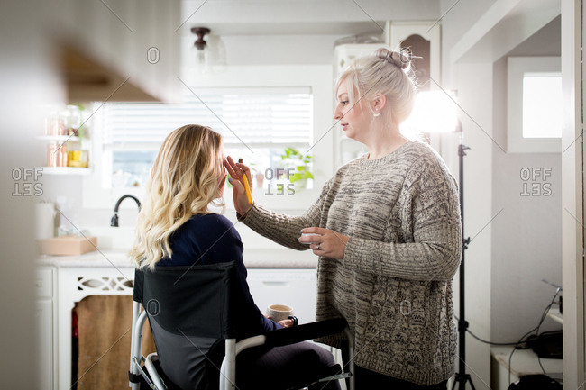Makeup artist applying eye shadow to woman