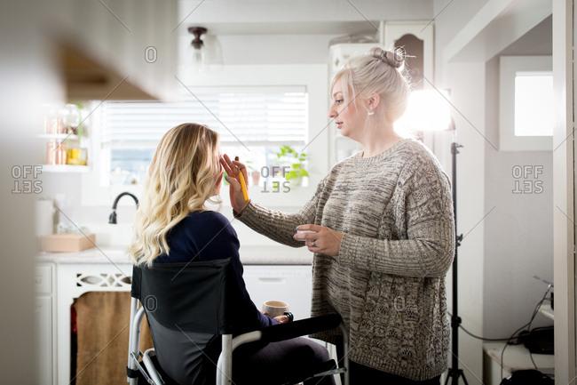 Makeup artist applying eye shadow to woman