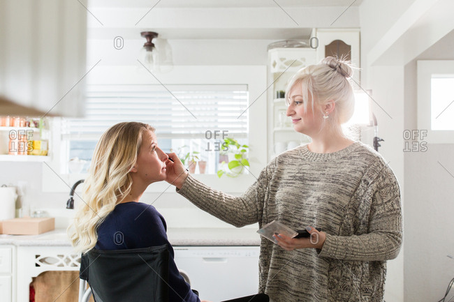 Woman applying eye shadow to client