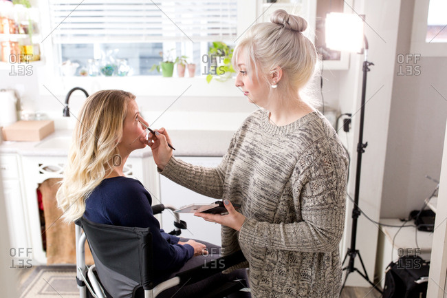 Woman applying eye makeup to client