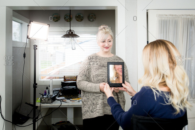 Woman looking at makeover in a mirror