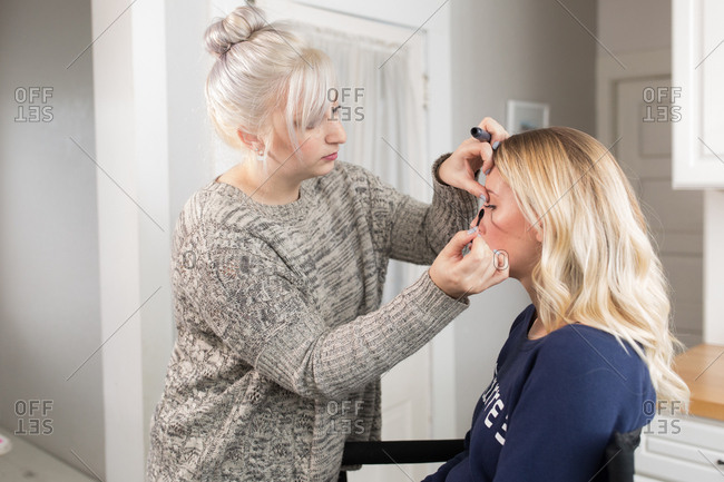 Makeup artist applying mascara to woman