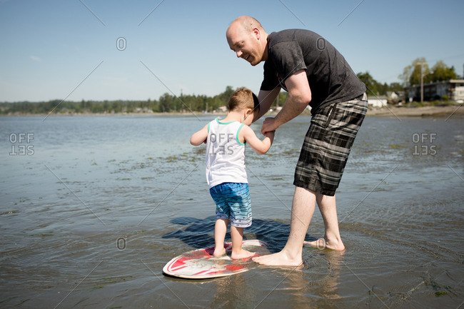 Father helping little boy ride a skim board