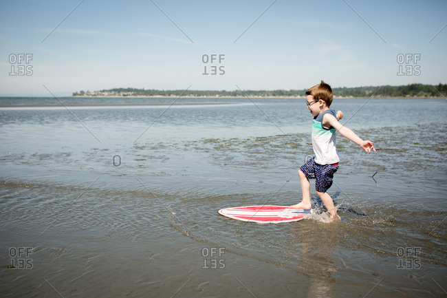 Little boy running and jumping onto a skim board