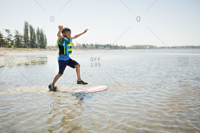 Boy running and jumping onto a skim board