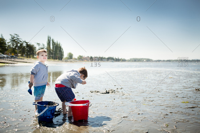 Two boys playing in the wet sand at a beach