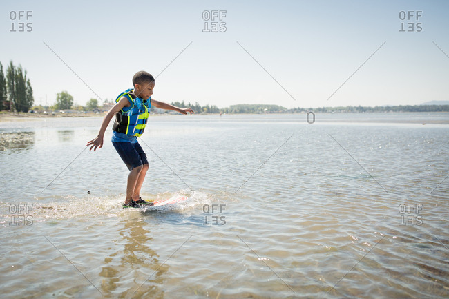 Boy riding a skim board