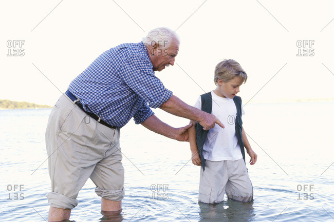 Grandfather and Grandson Wading In Water