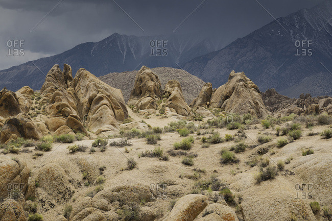Rock formations of the Alabama Hills with storm clouds over the Sierra Nevada Mountains in background, Eastern California, USA