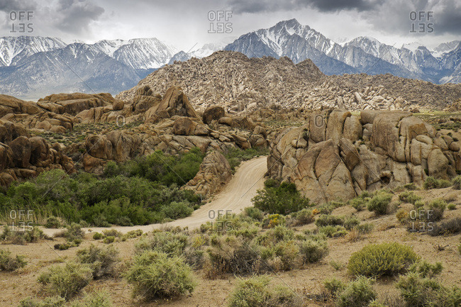 Dirt road through the Alabama Hills with the Sierra Nevada Mountains in the background in Eastern California, USA
