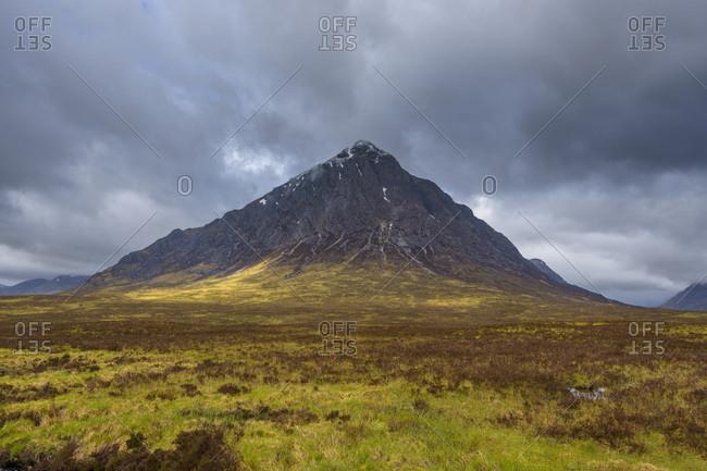 Mountain range Buachaille Etive Mor with dark cloudy sky at Glen Coe in Scotland, United Kingdom