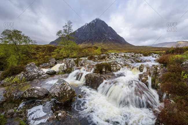 Waterfall on River Coupal and mountain range Buachaille Etive Mor at Glen Coe in Scotland, United Kingdom