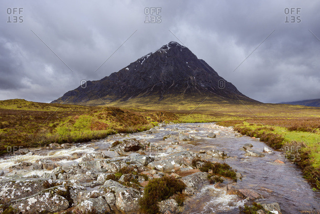 River Etive and mountain range Buachaille Etive Mor with dark cloudy sky at Glen Coe in Scotland, United Kingdom
