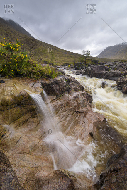Waterfall on River Coupal with overcast sky at Glen Coe in Scotland, United Kingdom