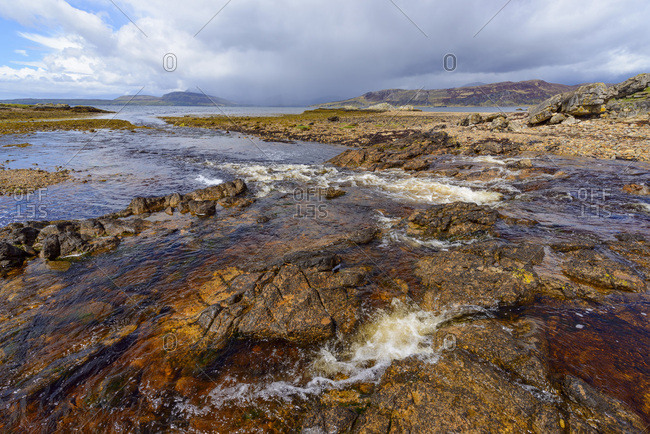 Rocky shoreline of a river flowing into the sea bay on the Isle of Skye in Scotland, United Kingdom
