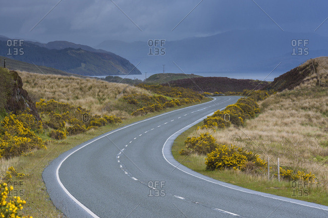 Winding country road with an overcast sky in springtime in the Isle of Skye, Scotland, United Kingdom