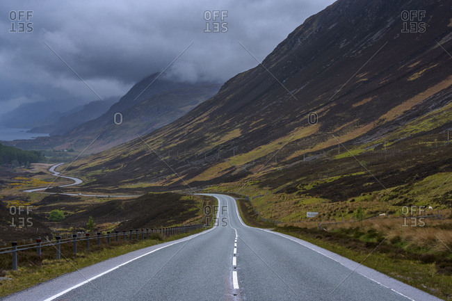 Storm clouds and typical Scottish country road through the highlands, Scotland, United Kingdom