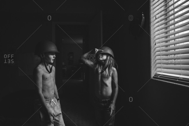 Two boys wearing army hats in black and white