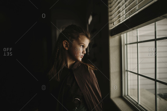 Little boy dressed in Halloween costume looking out window