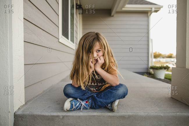 Little boy with long hair pouting on a porch