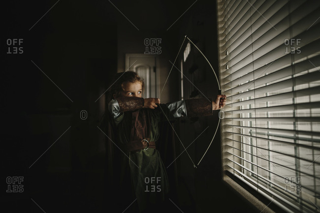 Little boy dressed in Halloween costume with boy by window