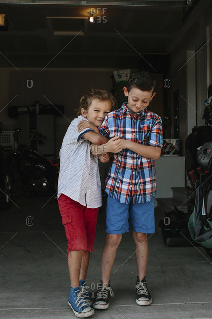Two brothers hugging in a garage