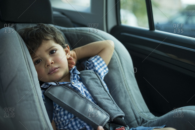 Portrait of toddler sitting in child's seat in a car