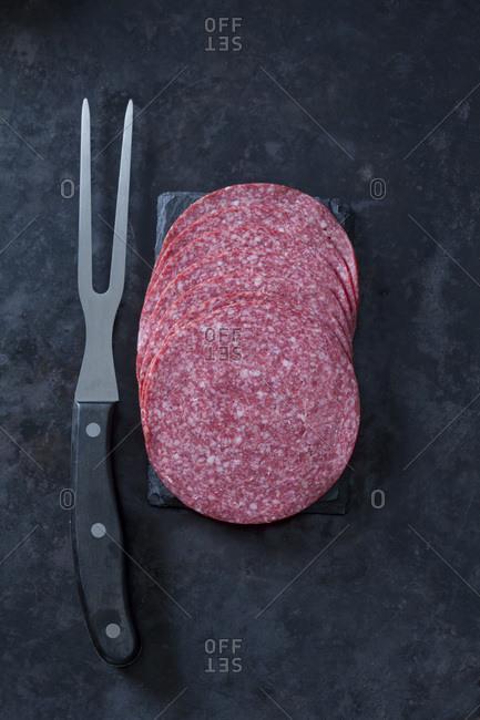 Sliced salami sausage with meat fork